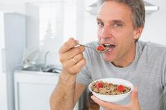 Stock Photo of Happy man eating cereal for breakfast in kitchen