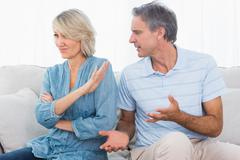 Man pleading with his wife after a fight - stock photo