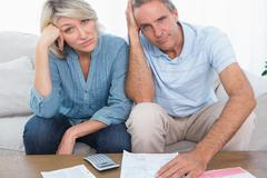 Anxious couple going over bills looking at camera Stock Photos