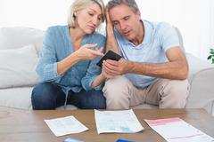 Worried couple going over their debt - stock photo