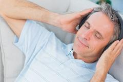 Man lying on couch listening to music with eyes closed Stock Photos