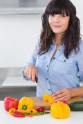 Pretty brunette slicing vegetables Stock Photos