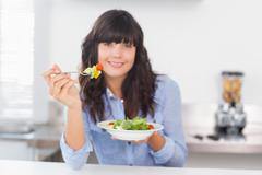 Stock Photo of Pretty brunette having a healthy salad for lunch