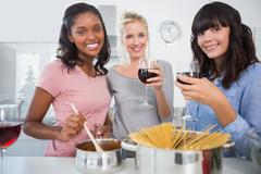 Cheerful friends making spaghetti dinner together and drinking red wine - stock photo