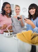 Happy friends making spaghetti dinner together and drinking red wine - stock photo