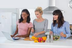 Smiling friends making salad and using laptop for recipe Stock Photos