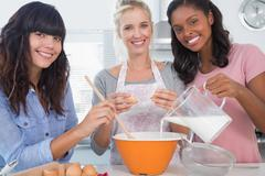 Smiling friends making pastry together looking at camera - stock photo