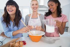Laughing friends making pastry together Stock Photos