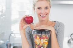 Stock Photo of Blonde woman leaning on her juicer full of fruit and holding red apple