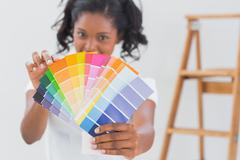 Excited woman showing colour charts - stock photo