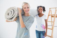Smiling housemates carrying rolled up rug - stock photo