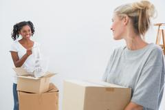 Stock Photo of Cheerful young housemates moving into new home