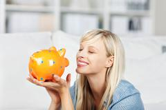 smiling woman looking at her piggy bank - stock photo