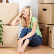 smiling woman surounded by cardboard cartons - stock photo