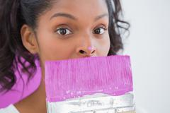 Pretty woman holding paintbrush with paint on her nose - stock photo