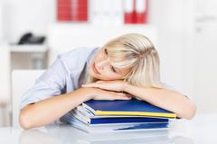 Overworked woman resting on office binders Stock Photos