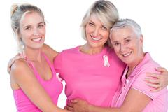 Women wearing pink tops and ribbons for breast cancer - stock photo