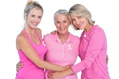 Happy women wearing pink tops and ribbons for breast cancer Stock Photos