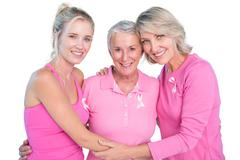 Embracing women wearing pink tops and ribbons for breast cancer Stock Photos