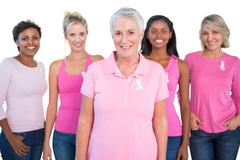 Diverse group of women wearing pink tops and breast cancer ribbons - stock photo