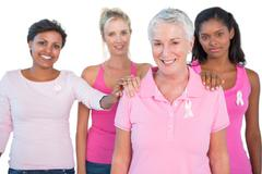 Supportive group of women wearing pink tops and breast cancer ribbons Stock Photos