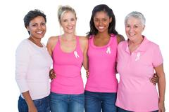 Smiling women wearing pink tops and breast cancer ribbons - stock photo