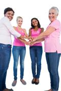 Happy women wearing breast cancer ribbons putting hands together smiling at Stock Photos