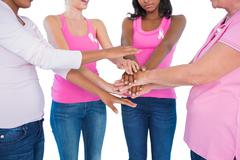 Women wearing breast cancer ribbons with hands together - stock photo