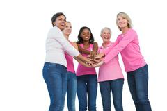 Women wearing breast cancer ribbons with hands together and smiling Stock Photos
