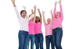 Cheering women wearing breast cancer ribbons - stock photo