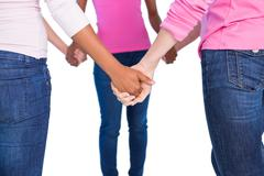 Women wearing pink for breast cancer holding hands - stock photo