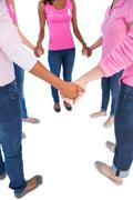 Women wearing pink and ribbons for breast cancer holding hands in a circle - stock photo