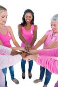 Stock Photo of Happy women wearing pink and ribbons for breast cancer putting hands together