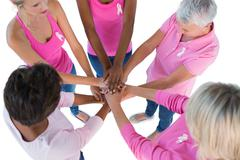 Group wearing pink and ribbons for breast cancer with hands together Stock Photos