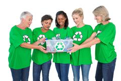 Team of female environmental activists holding box of recyclables Stock Photos