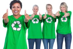 Happy women wearing green recycling tshirts giving thumbs up Stock Photos