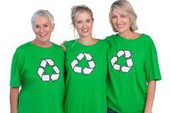 Three women wearing green recycling tshirts smiling at camera - stock photo