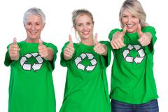 Three women wearing green recycling tshirts giving thumbs up - stock photo