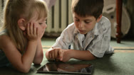 Stock Video Footage of Childs with tablet pc lying on the floor