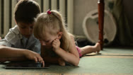 Stock Video Footage of Two Childs lying on the floor and playing with tablet pc