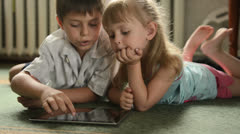 Stock Video Footage of Two Childs with tablet pc lying on the floor