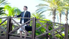 Businessman with briefcase on his vacation in tropical garden Stock Footage
