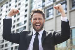 Young successful business man celebrating in city Stock Photos