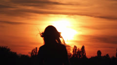 silhouette of a girl in the setting sun - stock footage