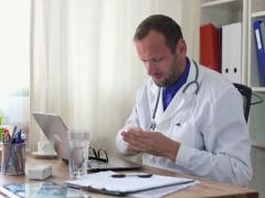 Male doctor taking pill for his headache NTSC Stock Footage