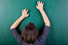 frustrated woman scratching chalkboard - stock photo