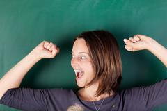 woman with arms raised shouting against chalkboard - stock photo