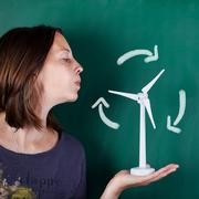 Woman blowing toy windmill against blackboard Stock Photos