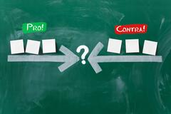 Arrows pointing at question mark with sticky notes on blackboard Stock Photos