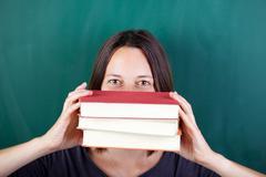 female teacher peeking over books against chalkboard - stock photo